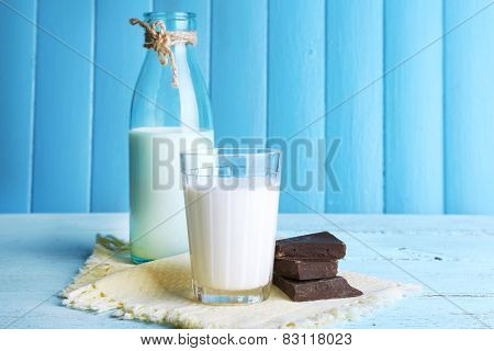 Glass and bottle of milk with chocolate chunks on color wooden planks background