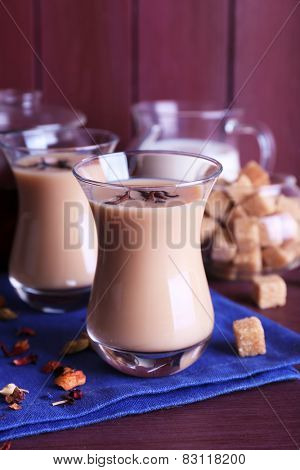 Black tea with milk and lump sugar and spices  in glassware on color wooden planks background