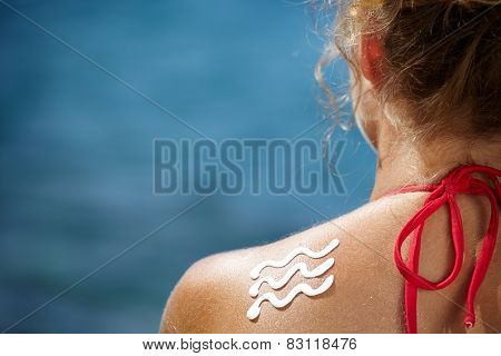Woman With Suntan Lotion At The Beach In Form Of The wave