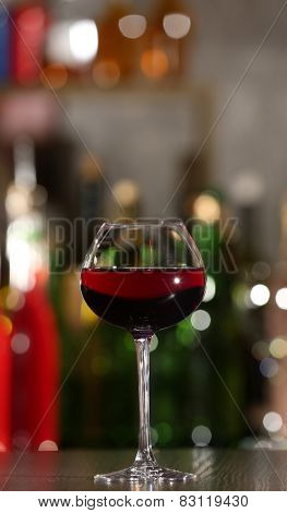 Glass of red wine with bar on background