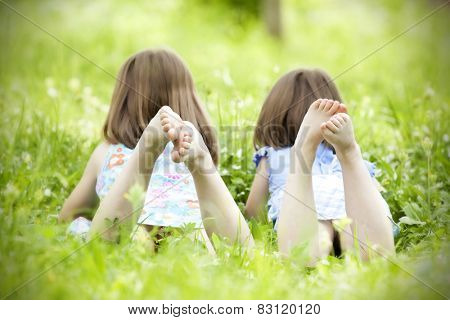 Happy children lying on green grass outdoors in the grass
