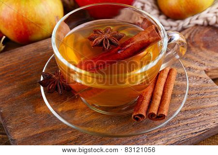 Composition of  apple cider with cinnamon sticks, fresh apples, warm scarf and autumn leaves on wooden background