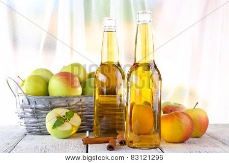still life with apple cider and fresh apples on wooden table