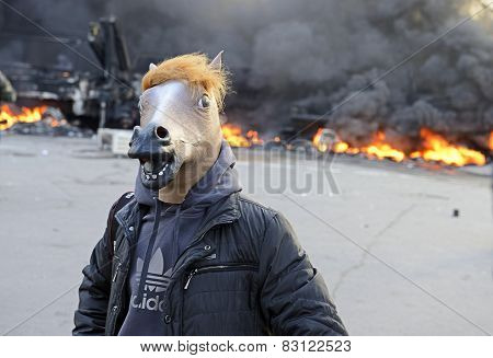Protestor In Mask On  Ablaze Car Background