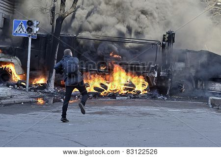 Young Protestor Near Ablaze Car Tosses A Stone