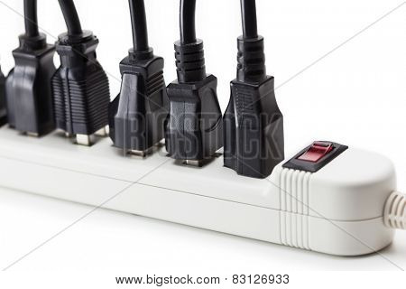 Many black electrical plugs connected to a power strip or extension block. Isolated on white.