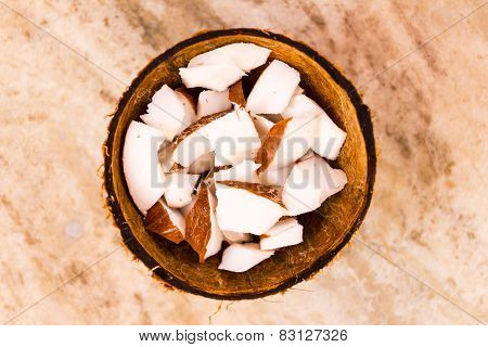 Close-up view of evenly chopped small piece of coconut kept inside shell