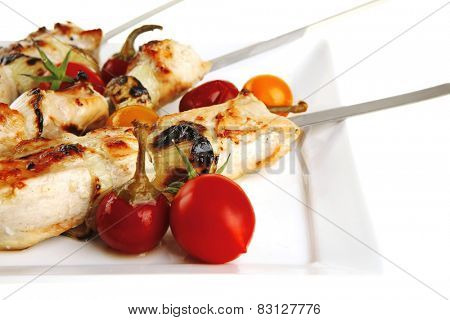 fresh grilled chicken shish kebab on white platter