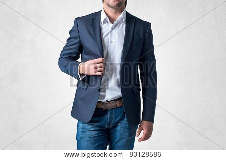 Man in trendy suit  standing alone holding his jacket with confidence
