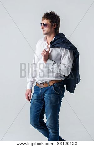 Serious confident cool attractive guy in jeans holding suit jacket on his shoulder looking away left