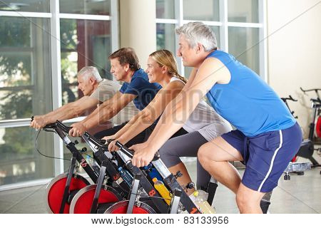 Spinning class with four happy senior people in a gym