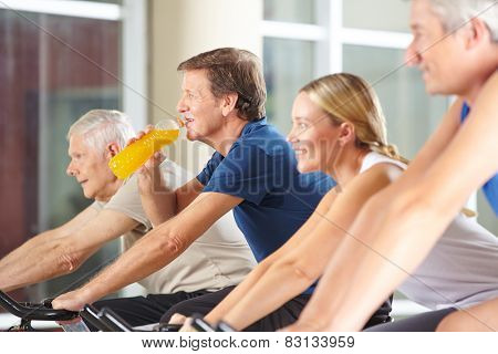 Thirsty man drinking orange juice in gym on spinning bike