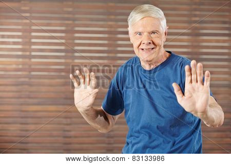 Old man doing gymnastics in fitness center and moving his hands
