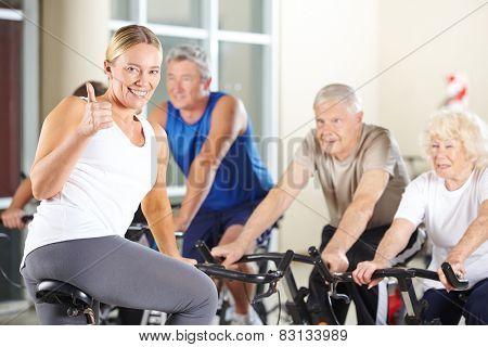 Happy fitness instructor in gym holding thumbs up with senior group
