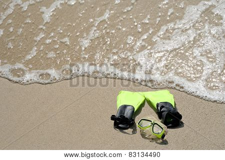 Concept or conceptual snorkeling and swimming gear on sand beach in exotic island in summer background with ocean waves