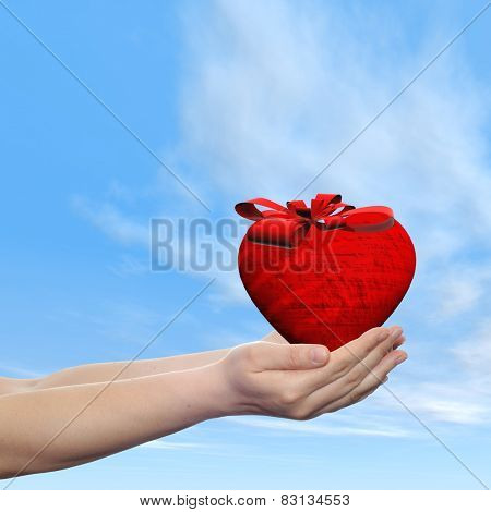 Concept or conceptual 3D red abstract heart sign or symbol with ribbon held in hands by a man, woman or child on blue sky background