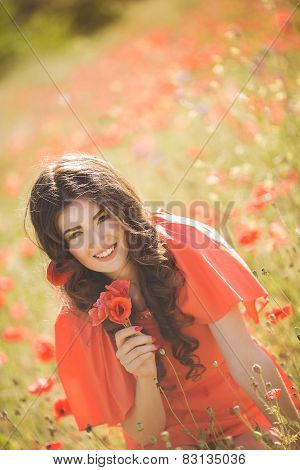 Young beautiful woman walking through a poppy field in summer