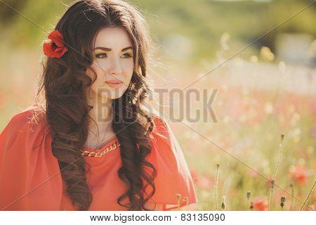 Young beautiful woman walking through a poppy field in summer