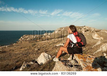 Woman Hiker Sits On Seaside Mountain Rock
