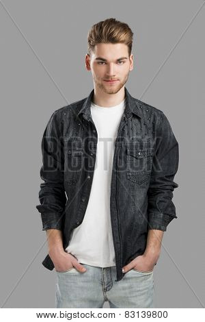 Good looking young man smiling with hands in the pockets, isolated over a gray background