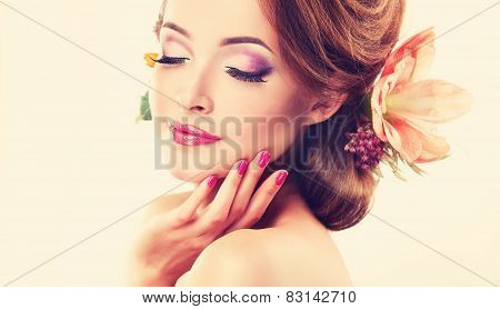 Spring freshness. Girl with delicate pastel flowers in curly hair