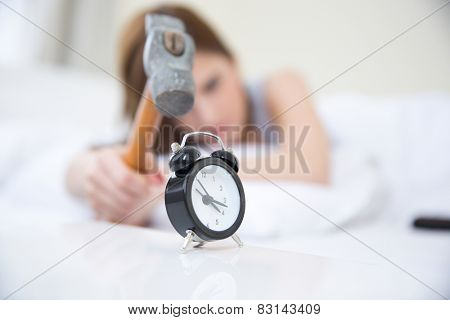 Woman not wanting to get up, taking a hammer to her alarm clock. Focus on clock