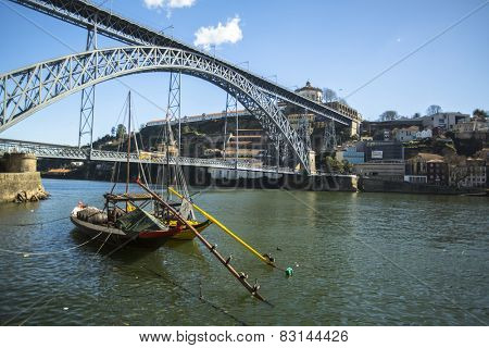 PORTO, PORTUGAL - FEB 17, 2015: Ribeira, traditional boats at Douro river in Old Town, Luiz iron bridge in background. In 1996, UNESCO recognised Old Town of Porto as a World Heritage Site.