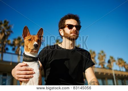 Strong Bearded Man In Sunglasses Sitting In Sand With Friend Dog Breed Basenji And Looking Into The