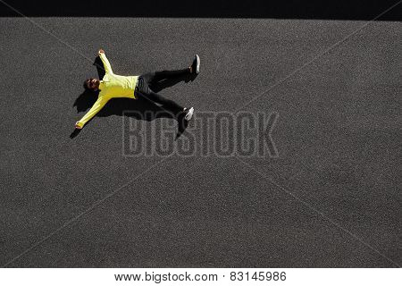 Top View Runner In Yellow Sportswear Resting Lying On A Black Asphalt After Running. Jogging Man Tak