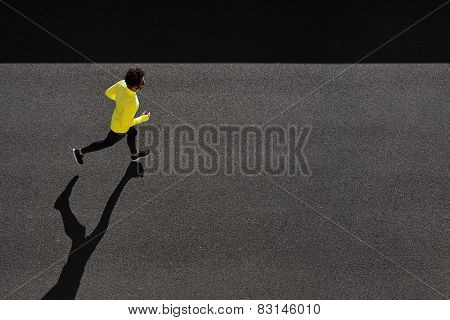 Top View Athlete Runner Training At Black Road In Yellow Sportswear. Muscular Fit Sport Model Sprint