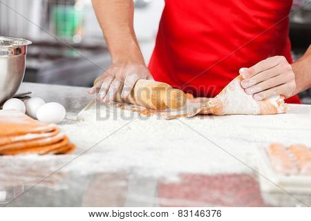 Midsection of male chef holding rolling pin while preparing ravioli pasta at counter in commercial kitchen