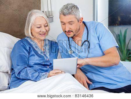 Male nurse discussing over digital tablet with senior woman in bedroom at nursing home