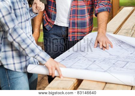 Midsection of male and female carpenters analyzing blueprint at site
