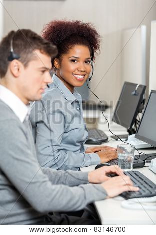 Portrait of happy young female telephone operator with her colleague in office