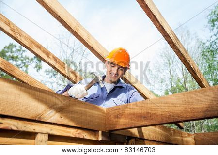 Low angle view of male worker hammering nail on incomplete timber cabin at site