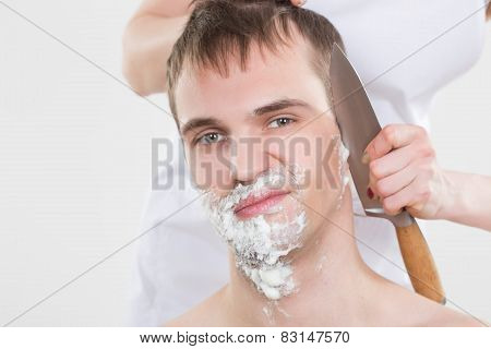 handsome man shaves a woman with a knife