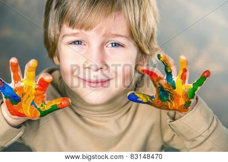 little boy hands painted  in colorful paints
