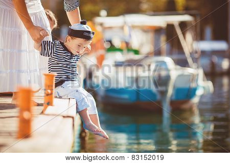 Mother and son having a good time together in the dock next to the yacht.
