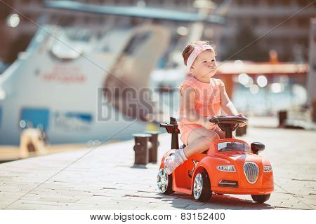 Little girl riding a children's car on the waterfront.