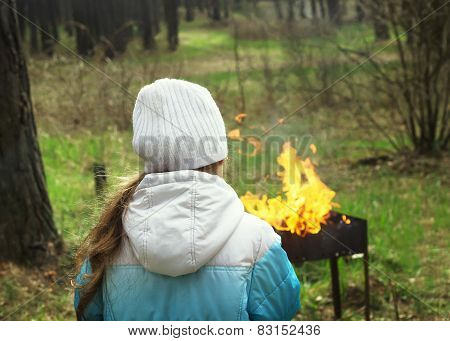 kid looking to old style metal campfire made ready for grilling