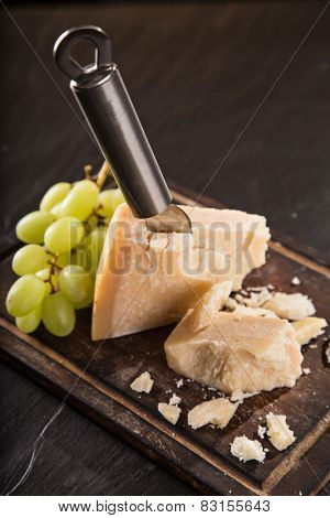 Parmigiano reggiano on wooden background, close-up.