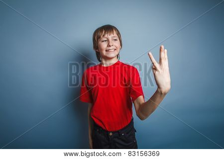 boy teenager European appearance in a red shirt showing thumbs d