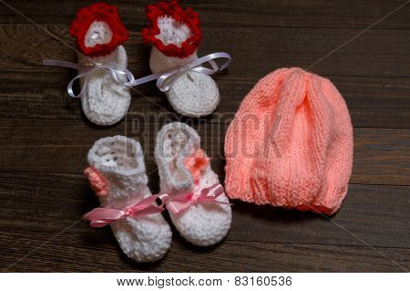 baby's bootee and cap on wooden background