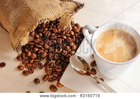 Cup Of Hot Coffee On Table And Sack With Coffee Beans Closeup