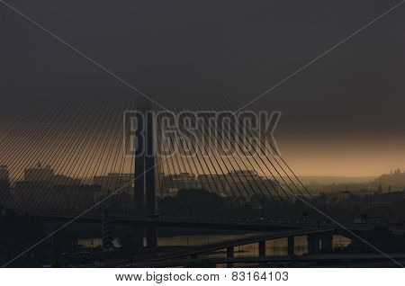 Cable bridge in low dark clouds before a storm