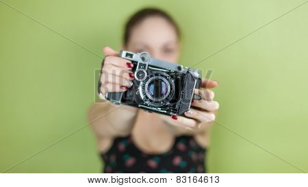 smiling girl with vintage  retro camera taking photo on green background