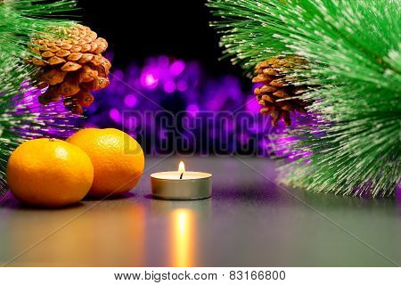 Christmas theme. Burning tea candle and  two mandarins between branches of larch with pine cone.