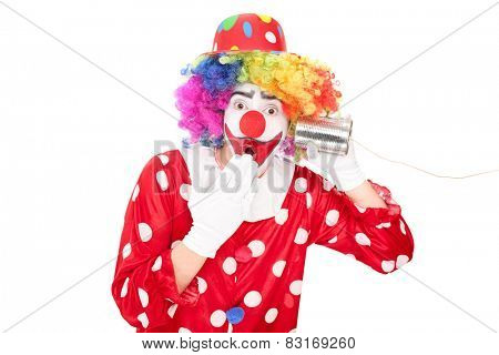 Surprised clown listening through a tin can phone isolated on white background
