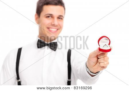 Young man proposing with a diamond ring with the focus on the ring isolated on white background