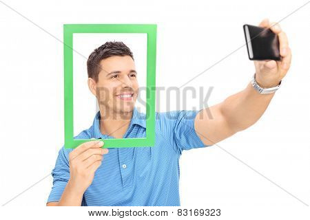 Man taking a selfie behind a picture frame with cell phone isolated on white background